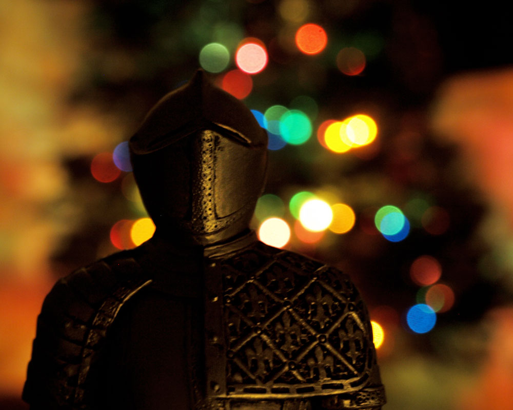 knight silhouetted against christmas tree bokeh