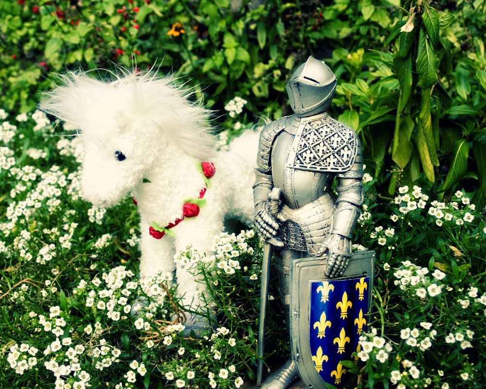 knight figurine in garden with white stuffed horse