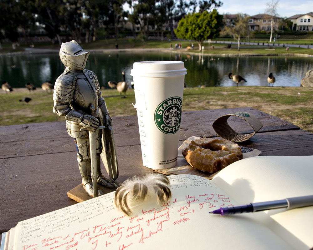 knight figure on picnic bench in park with starbucks cup and notebook
