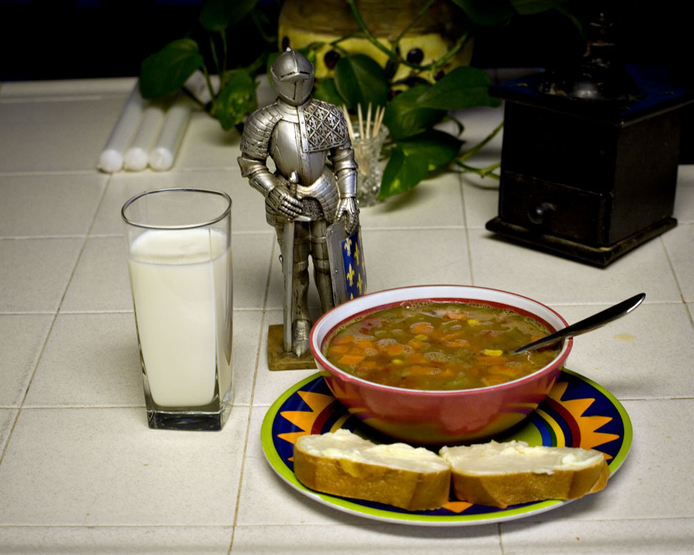 knight figure on counter with soup bowl and glass of milk