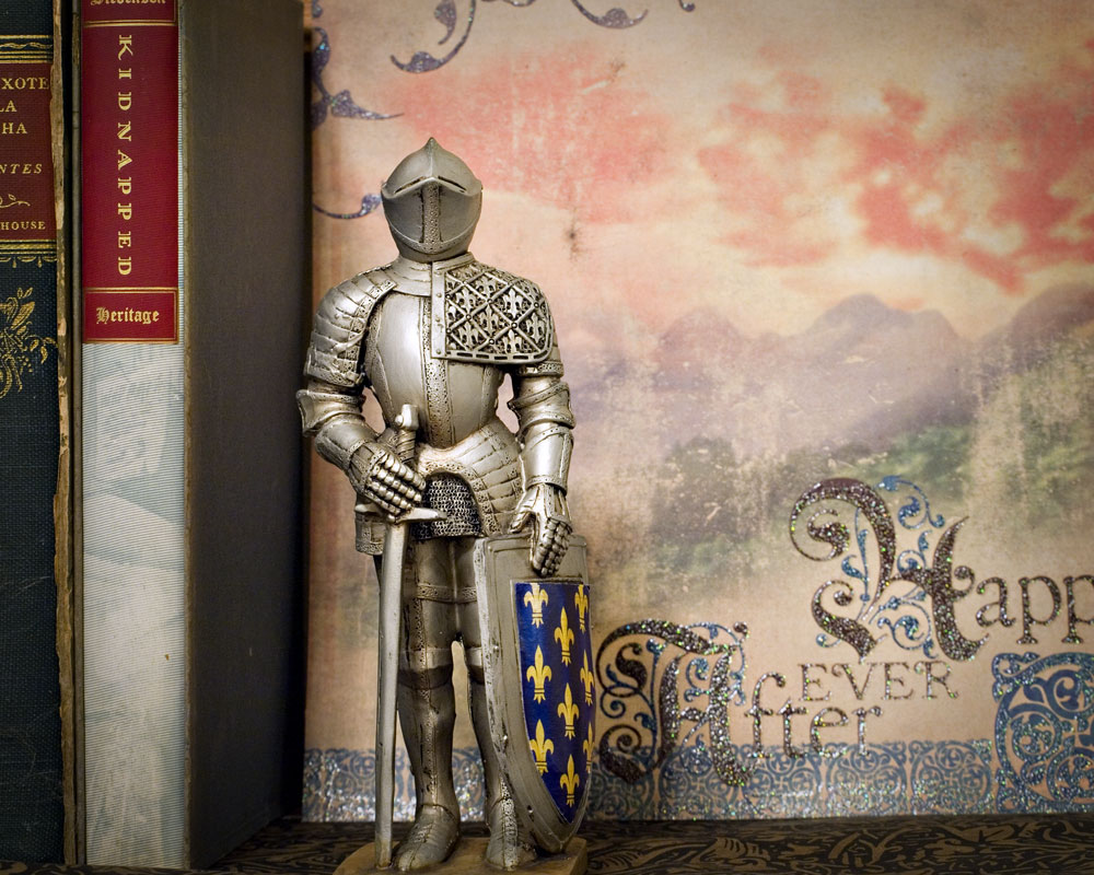 knight figure on shelf next to books with decorative paper background