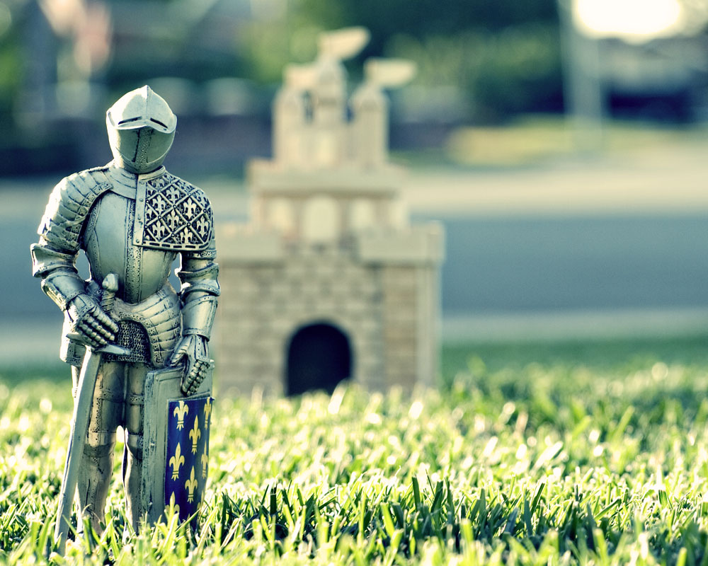 knight figure on lawn with small castle in background