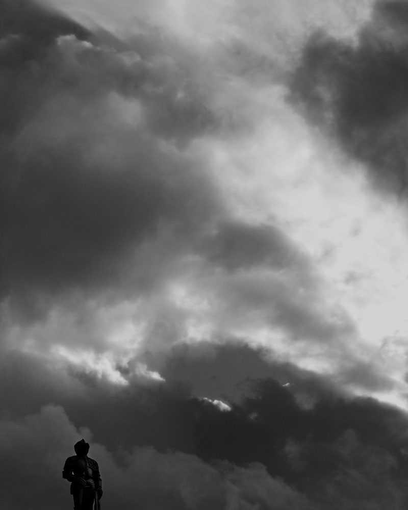 knight figure silhouetted against cloudy sky