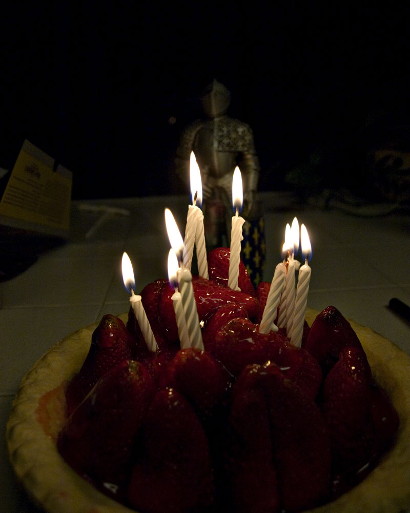 knight figure standing behind strawberry pie with candles