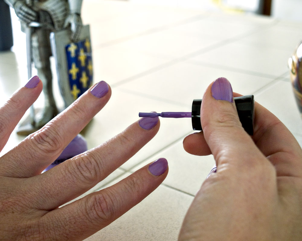 woman painting nails with knight figure in background
