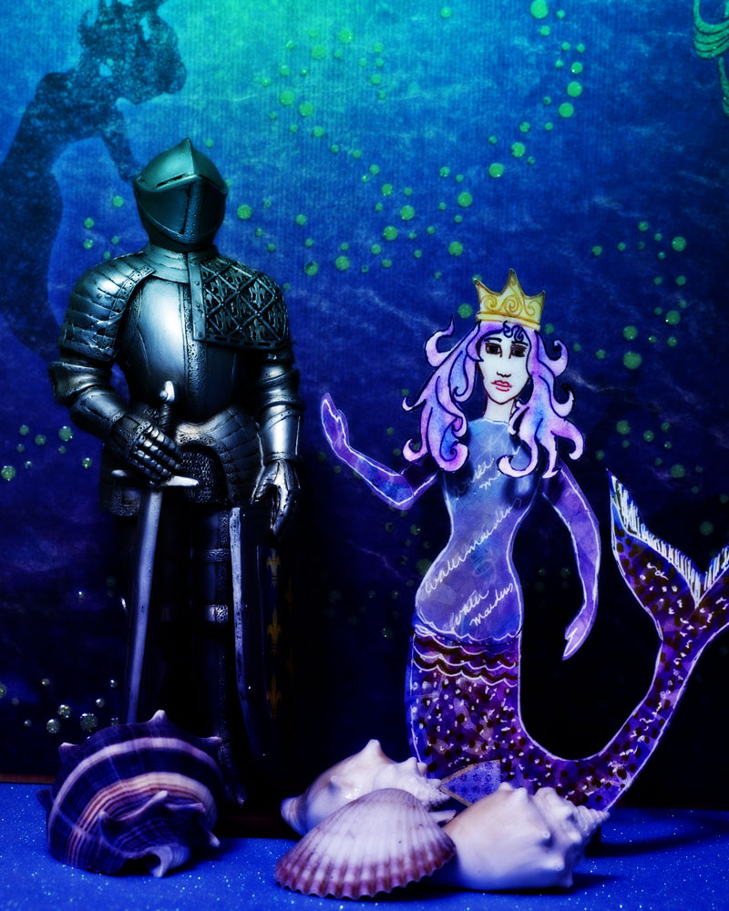 "knight figure in paper ""ocean"" with mermaid cutout"