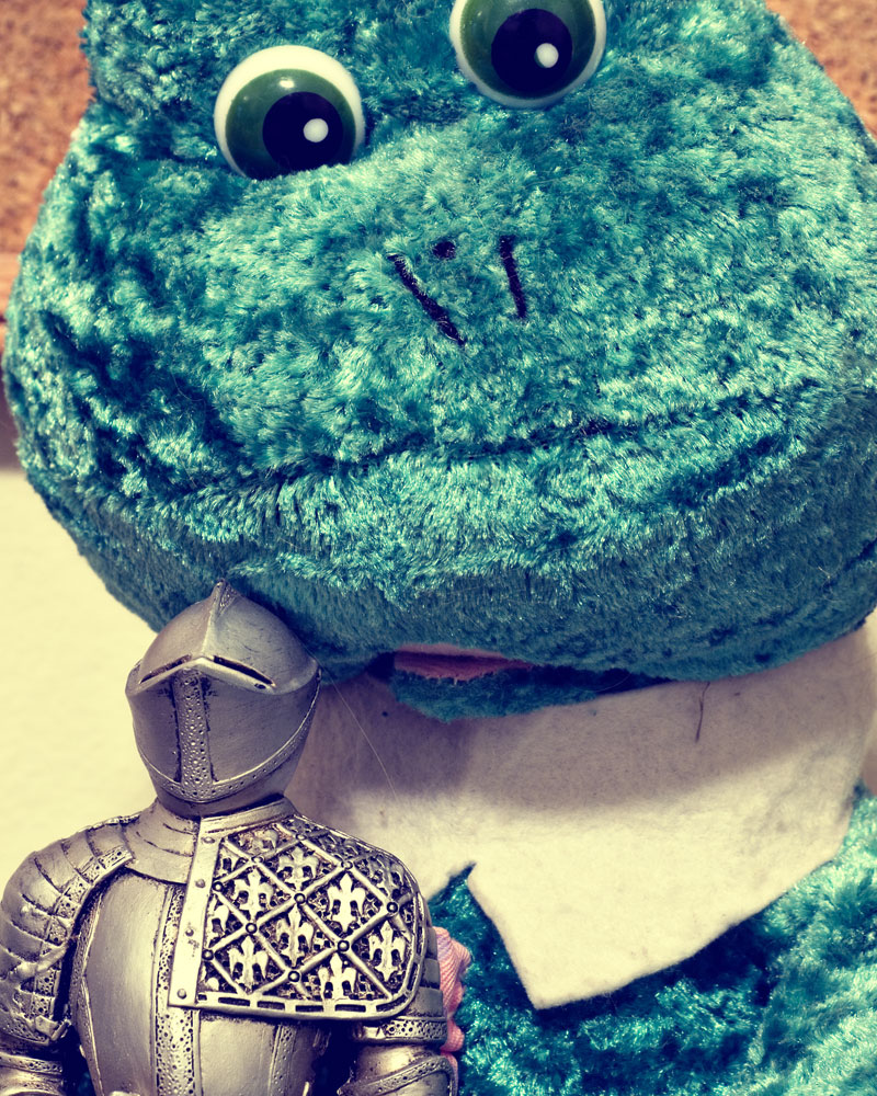 knight figure posing with large stuffed frog