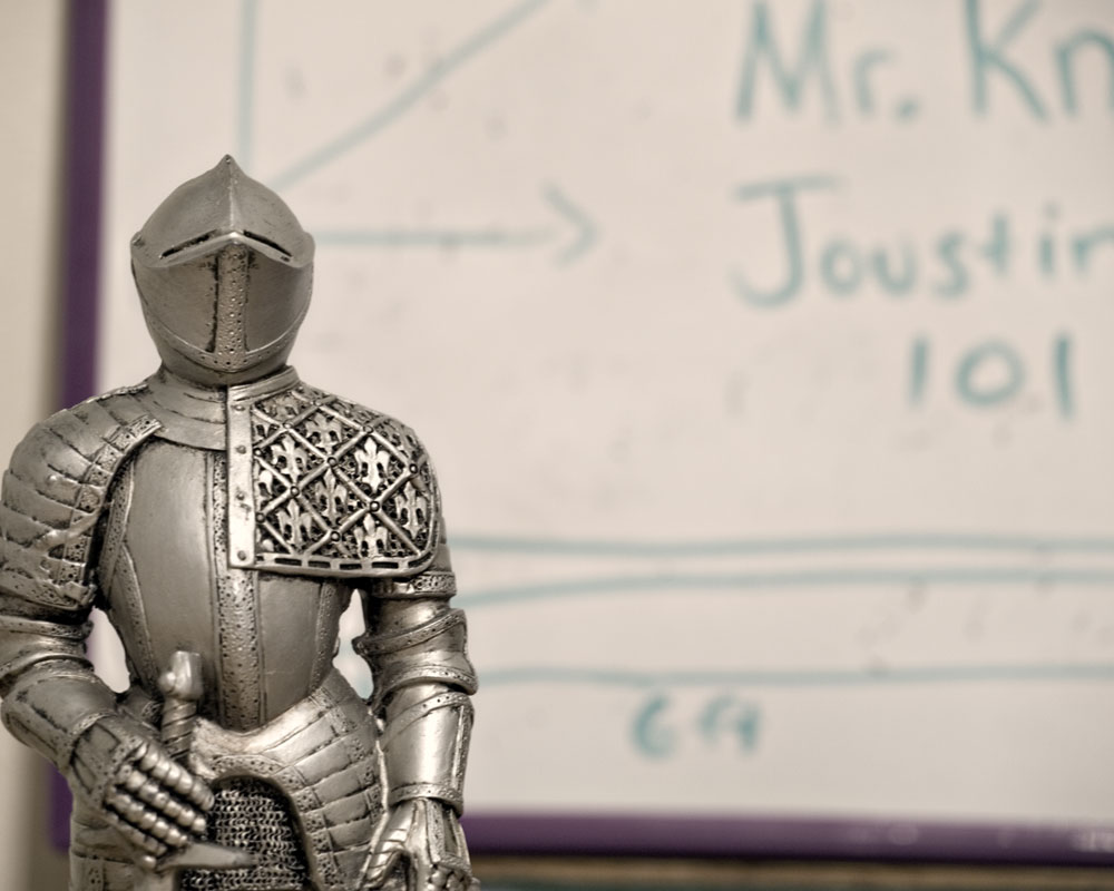"knight figure standing by white board with ""Jousting 101"" written on it"