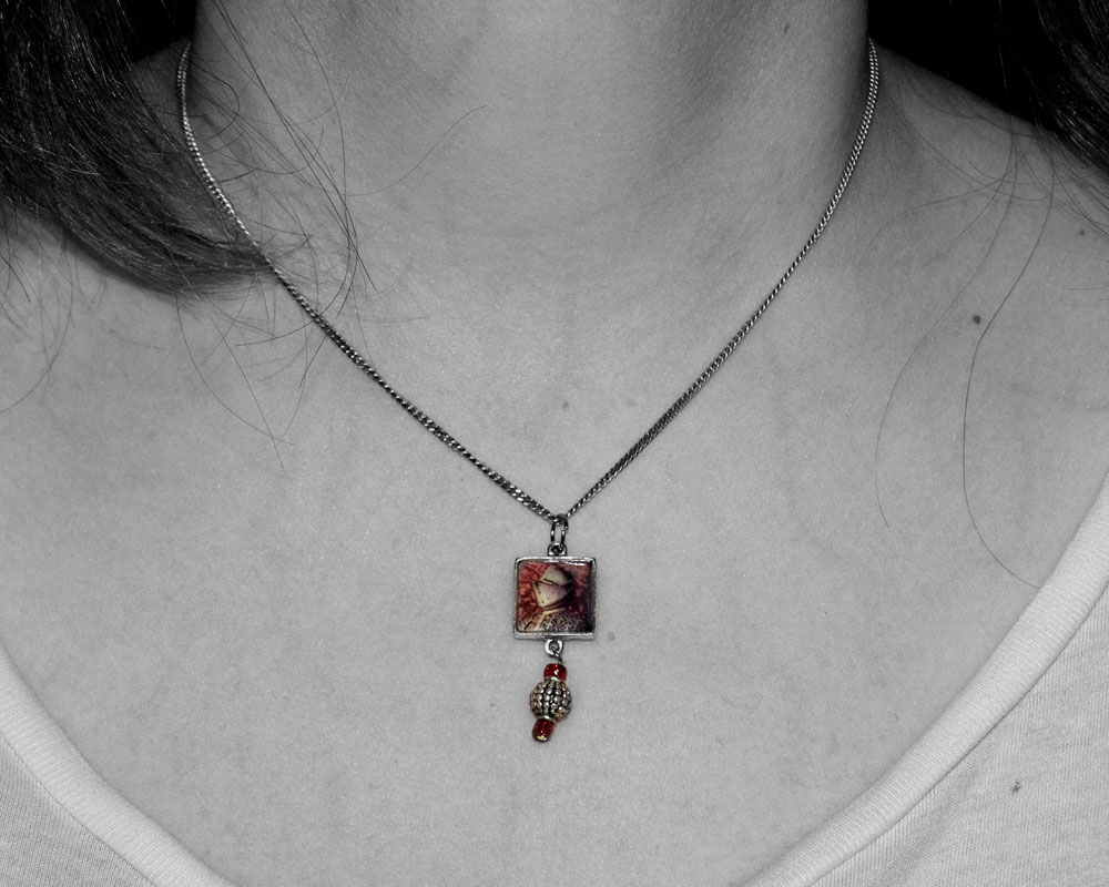 woman's neck wearing necklace that is a picture of knight figure